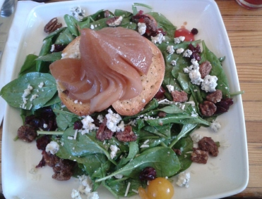 Poached chai tea pear atop baby spinach salad with all the fixings